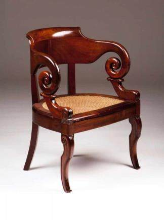 A Charles X style fauteuil Mahogany Carved decoration with scrolls Caned seat