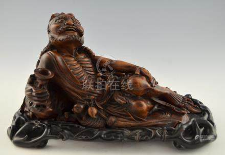 Chinese carved hardwood figure of a reclining bearded man, with a flask in one hand, on carved base,