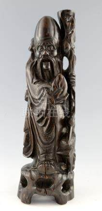 Chinese carved hardwood figure of Shou Lao, with his staff and holding a peach, inlaid wire