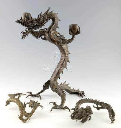 Chinese cast bronze two light candelabra in the form of a dragon rearing up on it's hind legs,