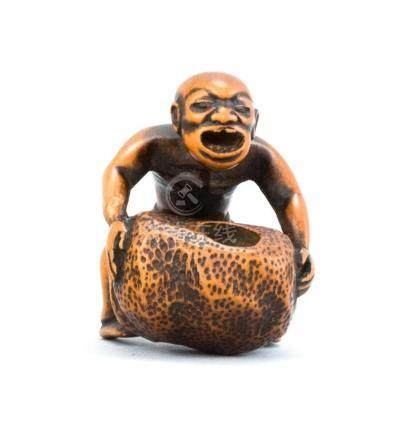JAPANESE WOOD NETSUKE Depicting a stone lifter