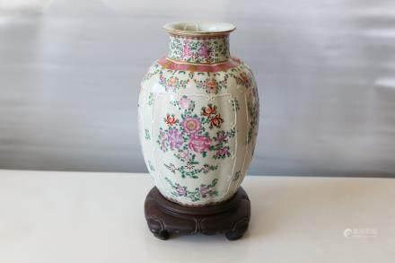 A chinese famille rose vase with hardwood base