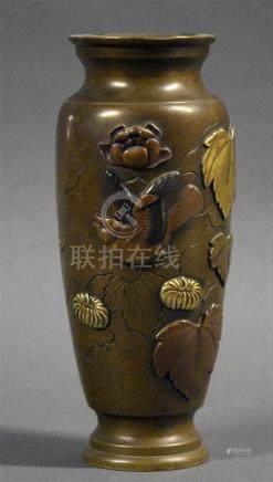 JAPON - Epoque MEIJI (1868 - 1912) Vase de forme allongée en bronze à patine brune à décor en taka bori et incrusté de cuivre doré d'oiseaux volant parmi les pivoines et chrysanthèmes.  H. 15 cm.  Expert: Cabinet Portier et associés