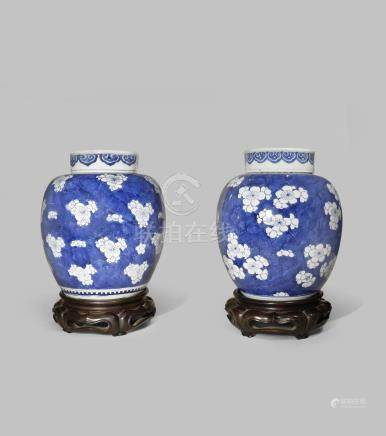 A NEAR PAIR OF CHINESE BLUE AND WHITE 'PRUNUS' JARS AND COVERS