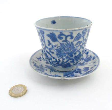 A Chinese blue and white cup and saucer, the cup decorated with lotus flower head and scroll,