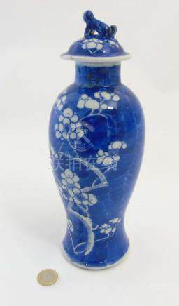 A blue and white Oriental lidded vase of baluster form, decorated with white Prunus flowers to body,