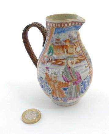 A Chinese Famille Rose jug with woven handle depicting an oriental family in a pagoda garden scene,