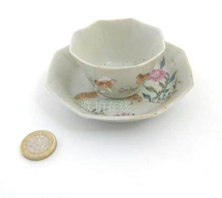 A Chinese Famille Rose octagonal cup and saucer depicting partridges amidst peonies on white ground,