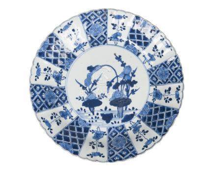 A Chinese porcelain plate, Kangxi, late 17th century, painted in underglaze blue with flowering