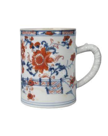 A Chinese porcelain mug, 18th century, painted in the imari palette with stylised rockwork, plants