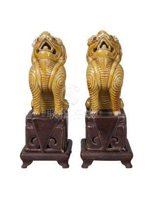 A pair of Chinese porcelain Buddhist lions, 18th century, both modelled seated on brown-glazed