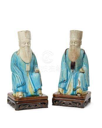 A pair of Chinese porcelain officials, 18th century, modelled seated, wearing turquoise robe,