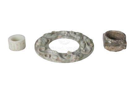 Three Chinese green hardstone carvings, 20th century, comprising a large ring incised with peony
