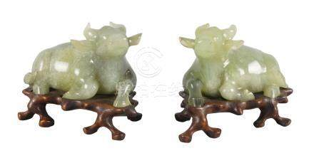 A pair of Chinese green hardstone buffalo, 20th century, each carved in recumbent pose, on fitted