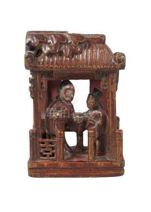 A Chinese painted and lacquered wood carving, late 19th century, depicting two figures beneath a