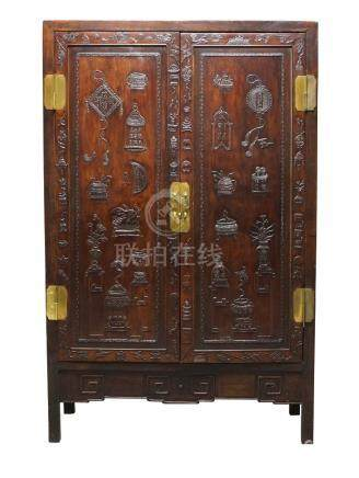 A Chinese huali wood cabinet, 19th century, with pair of doors carved in low relief with