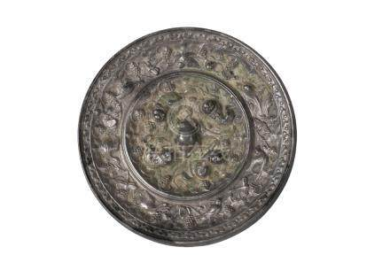 A Chinese silvered bronze 'Lion and Grape' mirror, Tang dynasty, with central crouching lion knop,