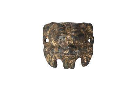 A Chinese gilt bronze applique, Han dynasty, finely modelled as a horned Buddhist lion mask, 4cm x