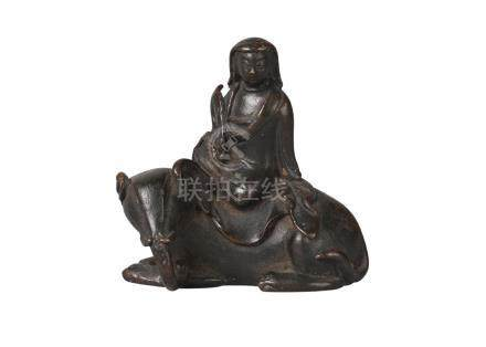A Chinese bronze scroll weight, Ming dynasty, 17th century, modelled as Guanyin seated atop a