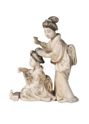 A Japanese ivory okimono of two ladies, late 19th century, carved as a geisha attending to the