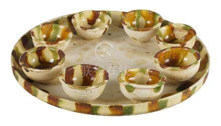 A Chinese pottery sancai glazed tray and eight cups, Tang dynasty style, the circular tray raised on