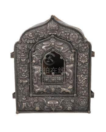 A Tibetan silver and copper backed gau, late 19th century, repousse decorated with Buddhist emblems,