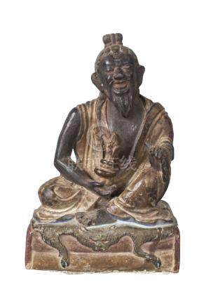 A Tibetan painted terracotta figure of Mahasiddha, early 19th century, depicted seated on a