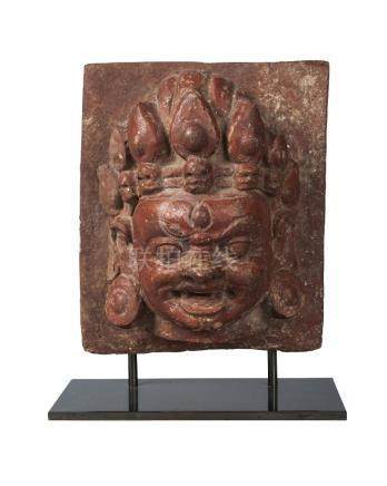 A Nepalese terracotta head of Bhajrava, early 20th century, wearing a crown adorned with skulls,