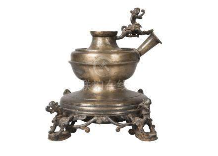 A Nepalese brass lamp base, 19th century, surmounted with a winged dragon and cast with four