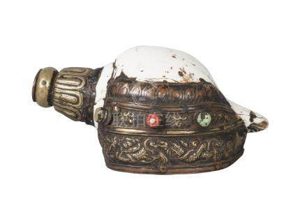 A tibetan ritual conch shell, 19th century, with repousse brass mounts decorated with a sinuous