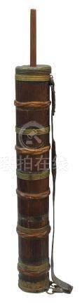 A Tibetan wood and brass mounted travelling grain mill, 19th century, with leather strap, 114cm high