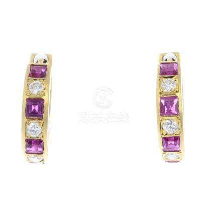 A pair of diamond and ruby hoop earrings. Each designed as an alternating square-shape ruby and