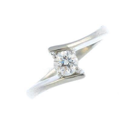 A platinum diamond single-stone ring. The brilliant-cut diamond, with crossover shoulders. Diamond