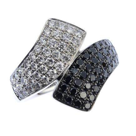 An 18ct gold diamond and gem-set ring. Of crossover design, the pave-set diamond and black gem