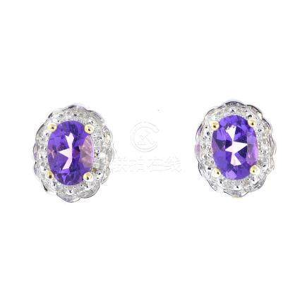 A pair of 9ct gold amethyst and diamond cluster earrings. Each designed as an oval-shape amethyst,