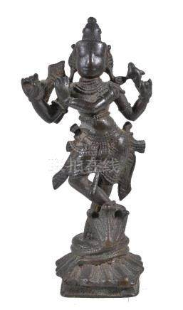 A bronze figure of Krishna playing the flute