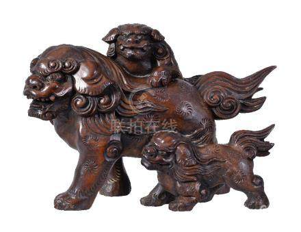 A Japanese wood Okimono of a large adult Shishi with two cubs