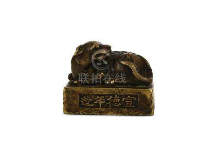 A CHINESE BRONZE 'QILIN' WEIGHT. Ming Dynasty. Cast as a seated the head turned to the left, the