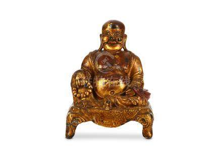 A CHINESE GILT-LACQUER BRONZE FIGURE OF BUDDHA. Ming Dynasty. The smiling, corpulent figure is