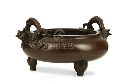 A LARGE CHINESE BRONZE TWIN HANDLED 'DRAGON' INCENSE BURNER. 17th Century. Of bombé form, supported