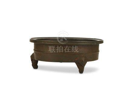 A CHINESE BRONZE INCENSE BURNER. 17th Century. The low cylindrical body encircled by a raised