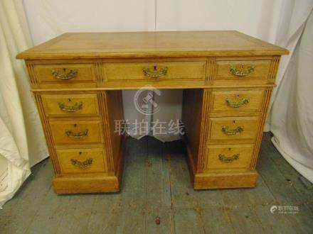 A light oak rectangular kneehole desk with leather top and nine drawers with brass handles