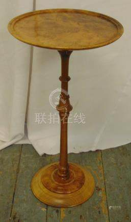 A walnut circular wine table on turned cylindrical stem and raised circular base