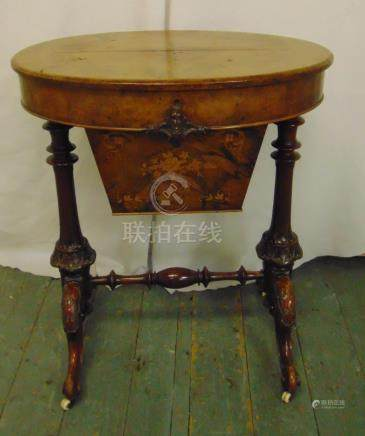 A Victorian oval sewing table on carved scrolling legs