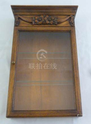 A wooden shaped rectangular glazed wall mounted cabinet