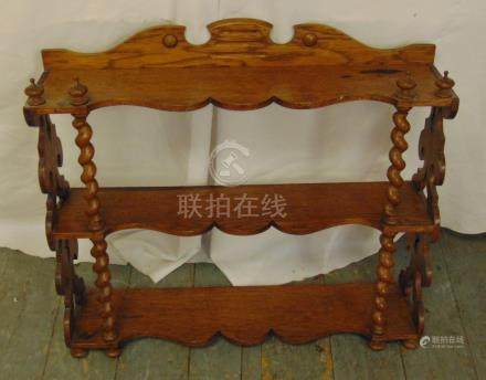 A mahogany three tier wall shelf with barley twist supports