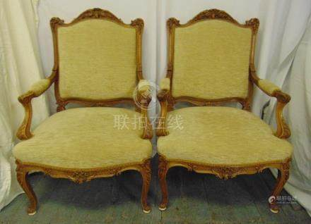 A pair of French style mahogany upholstered armchairs on four scroll legs