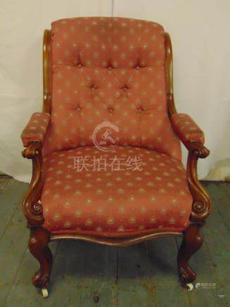 Victorian mahogany upholstered armchair on four scroll legs and castors