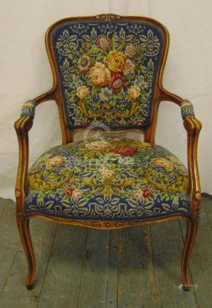 An occasional armchair with fluted scrolling arms and legs and tapestry upholstery