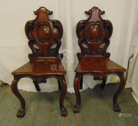 A pair of 19th century mahogany hall chairs, with carved back on scroll legs with paw feet